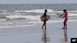 Dua orang anak siap bermain selancar di pantai North Carolina, AS, di mana sudah beberapa kali terjadi serangan oleh hiu di sana (foto: dok).