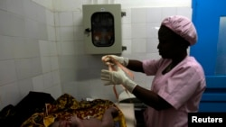 FILE - A midwife prepares to measure a newborn baby at the general hospital in Man, western Ivory Coast, July 4, 2013.