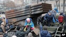 지난해 2월 우크라이나 정부군이 빼앗은 러시아산 대포가 키예프 거리에 전시되어 있다. 어린아이들이 대포에 올라타 구경하고 있다. (자료사진)