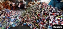 Government workers from the Bureau of Customs destroy counterfeit footwear products in Manila February 24, 2015. A government statement said over 150,000 pairs of fake shoes and slippers of various brands including Nike, Adidas, Converse, Sketchers, North