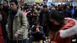 Hành khách chờ lên tàu tại một nhà ga ở Bắc Kinh ngày 31/1/2016.