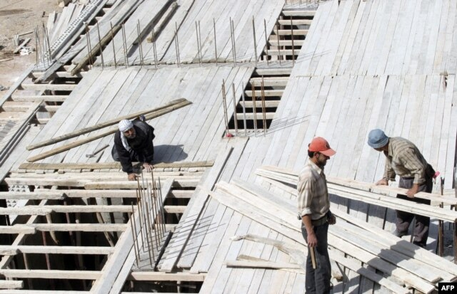 FILE - Members of a construction crew work at a site for new apartment buildings in Damascus, Syria.