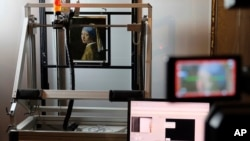 "FILE - In this photo dated Monday, Feb. 26, 2018, a macro XRF scanner is used to study in minute detail the surface of Johannes Vermeer's 17th century masterpiece ""Girl with a Pearl Earring"", at the Mauritshuis museum in The Hague, Netherlands. (AP Photo/Mike Corder, FILE)"