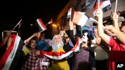 Iraqis celebrate while holding national flags in Tahrir square in Baghdad, Iraq, July 10, 2017.
