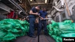 Ensign Sean Standard and Logistics Specialist 2nd Class Ray Sanders take inventory of a cache of more than 1,000 AK-47 automatic rifles in the hangar bay of the guided-missile destroyer USS Jason Dunham, seized from a traditional dow in the Gulf of Aden, Aug. 28, 2018.