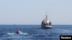Một chiếc thuyền của Việt Nam (trái) bị tàu Trung Quốc đâm và chìm gần quần đảo Hoàng Sa đang tranh chấp.