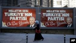 """一位妇女走过以土耳其总理耶尔德勒姆为背景,写有""""人们的声音,土耳其的党,已经十五岁了""""的标语(2016年8月15日)。"""