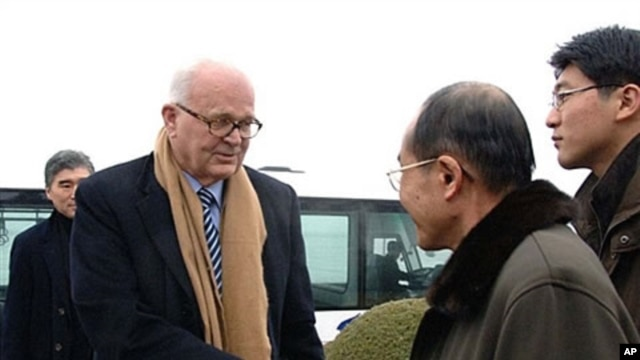 Stephen Bosworth (l), US special envoy to North Korea, shakes hands with an unidentified North Korean official upon his arrival at Pyongyang airport, 08 Dec 2009