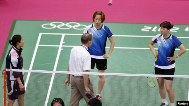 Tournament referee Torsten Berg (3rd R) speaks to players from South Korea (in blue) and Indonesia (in red) during their women's doubles group play stage Group C badminton match during the London 2012 Olympic Games at the Wembley Arena July 31, 2012.