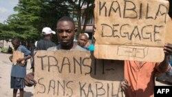 """Des manifestants tiennent des affiches avec la mention """"Kabila dégage"""" et """"la transition sans Kabila"""" près de la résidence de l'opposant Félix Tshisekedi, à Limete, Kinshasa, RDC, 30 novembre 2017."""