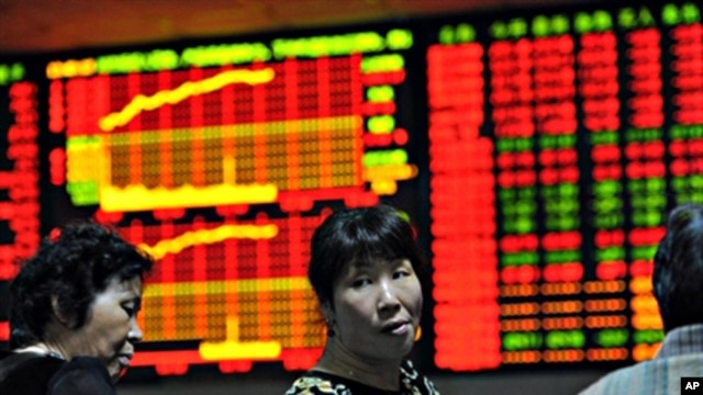 FILE - Chinese investors monitor their stock prices at a security firm in Hefei, east China's Anhui province.
