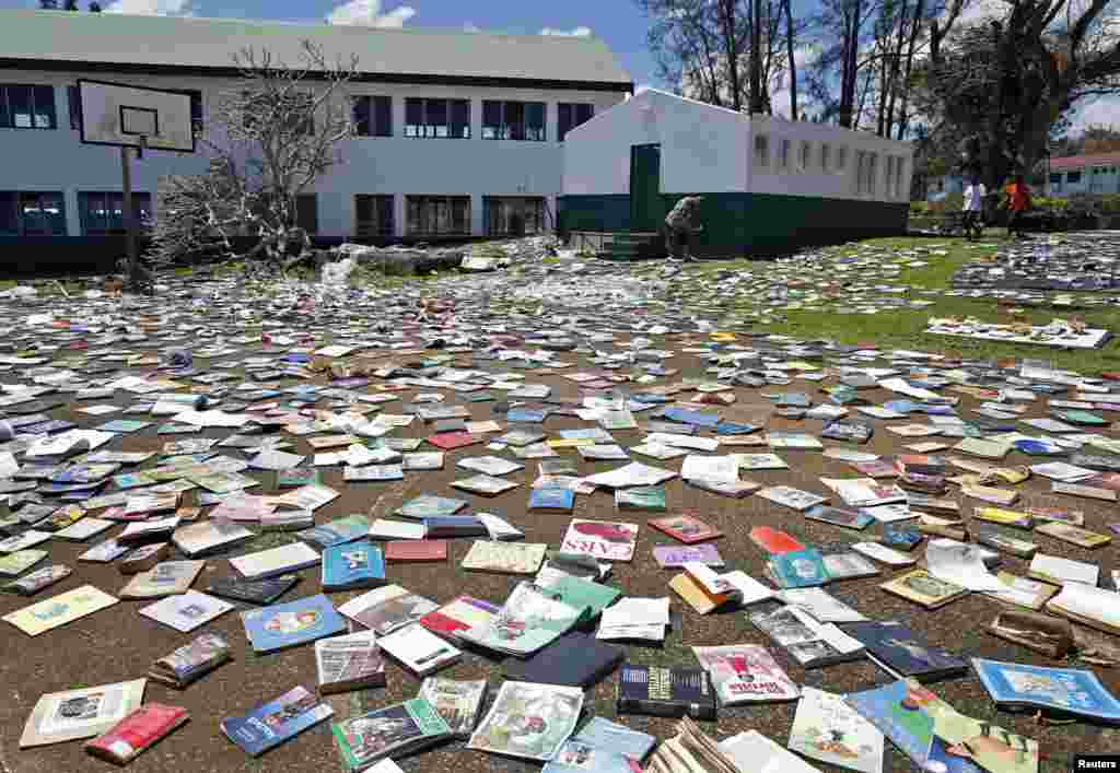Paul Alexander Hatyay (C), the headmaster and teacher of Central School puts books out to dry in the sun after the roof of the school's library was blown away by Cyclone Pam in Port Vila, the capital city of the Pacific island nation of Vanuatu.