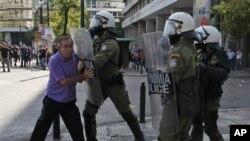 希腊防暴警察用护盾推搡参大罢工的一名老年抗议者