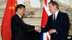 (资料图)英国首相卡梅伦与中国国家主席习近平在去年伦敦举行的英中商业峰会上握手。