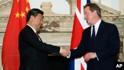 FILE - British Prime Minister David Cameron, right, shakes hands with China's President Xi Jinping, at the UK-China Business Summit in Mansion House, central London, Oct. 21, 2015