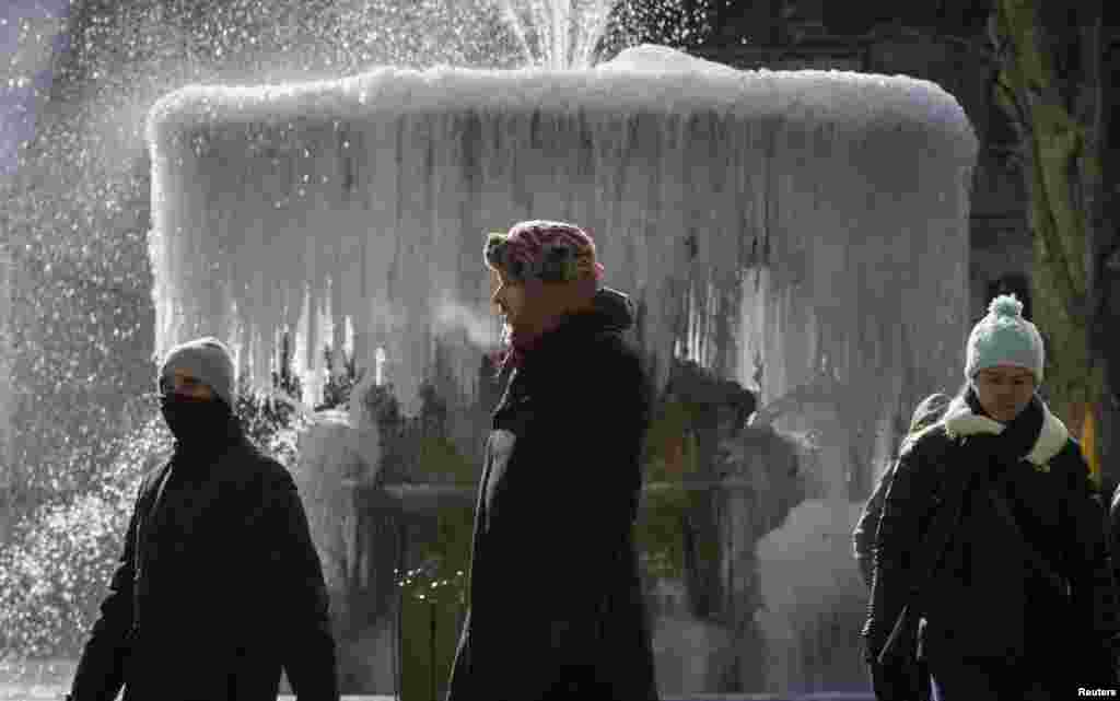 People walk past the ice-covered Josephine Shaw Lowell Memorial Fountain, in Bryant Park in Manhattan, New York City. Schools in many large cities closed on Thursday as freezing temperatures and harsh winds swept across central and eastern U.S. states for a third day in a row.