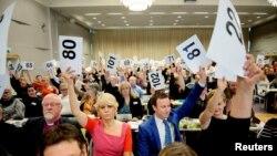 Le chef de file du Conseil norvégien Eglise Kristin Gunleiksrud Raaum, en rouge, et le président du conseil diocésain d'Oslo Gard Sandaker-Nielsen, à droite, votent sur une proposition visant à permettre le mariage de même sexe au sein de l'Eglise de Norvège, à Oslo, le 11 Avril 2016. (REUTERS/Ole Martin Wold)