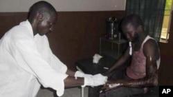 Un médecin soigne un étudiant à l'hôpital de Potiskum au Nigeria, qui a été blessé dans une attaque contre un établissement d'enseignement secondaire à Mamudo, ayant fait au moins 29 morts, le 6 juillet 2013.(AP Photo/Adamu Adamu)