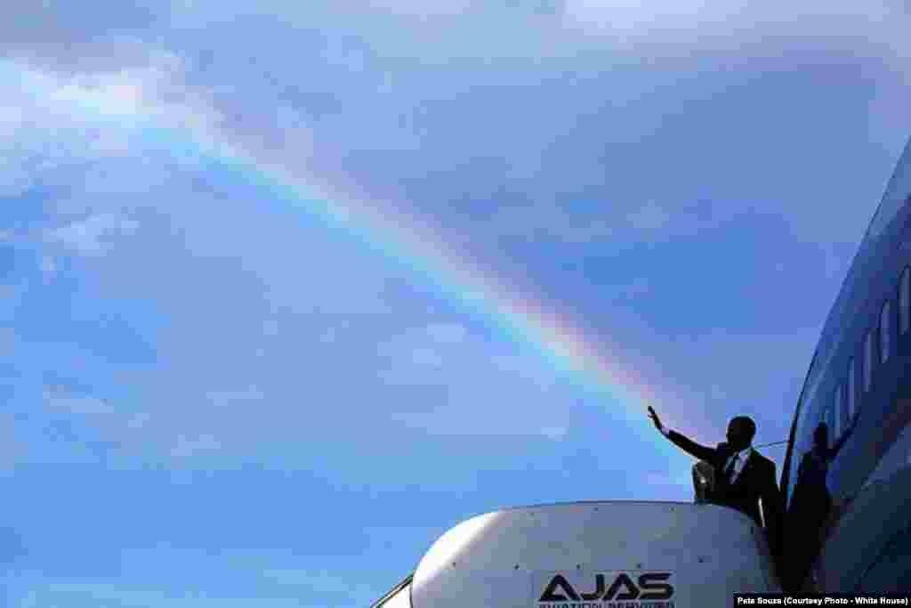 Le président américain salue la foule alors qu'un arc-en-ciel se forme dans le ciel, à Kingston, en Jamaïque, le 9 avril 2015.