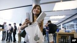 ລູກຄ້າຄົນນຶ່ງ ໃນຮົງກົງ ເອົາໂທລະສັບ iPhone 5 ທີ່ລາວຫາກໍຊື້ ອອກມາໃຫ້ເບິ່ງ (21 ກັນຍາ 2012)