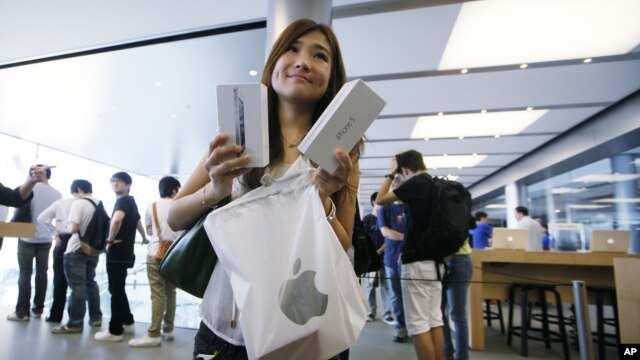 A customer shows her new iPhone 5 at the Apple store in Hong Kong, September 21, 2012.