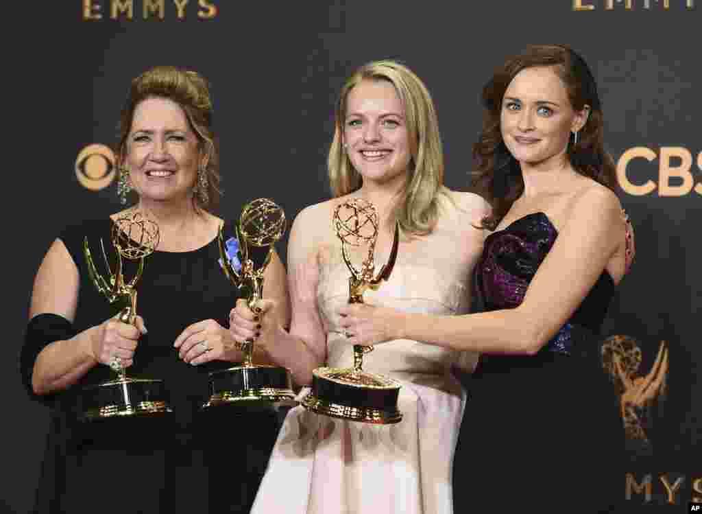 """Ann Dowd, desde la izquierda, gana premio como destacada actriz de reparto en una serie dramática, Elisabeth Moss, gana premio de mejor protagonista de una serie dramática, y Alexis Bledel, ganadora del premio a mejor actriz invitada en un drama para """"The Handmaid's Tale"""", posan en el 69th Primetime Emmy Awards, 17 de septiembre de 2017, en el Microsoft Theatre en Los Angeles."""