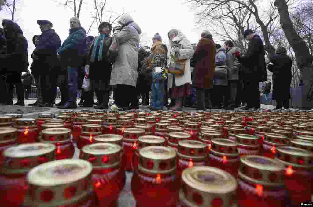 Lit candles are placed on the ground as people gather to attend a memorial service before the funeral of Russian leading opposition figure Boris Nemtsov, in Moscow, March 3, 2015.