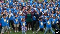 美国第一夫人米歇尔.奥巴马星期二和孩子们在白宫南草坪一起跳跃
