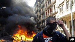 Demonstrator covers face during general strike in Barcelona, Spain, March 29, 2012.