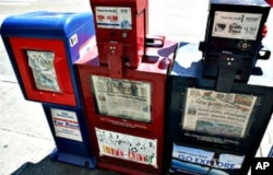 "This photo of newsboxes was taken in Seattle when it had two daily papers. Now the one in the middle box, the ""Post-Intelligencer"", is gone."
