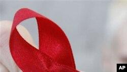 ** ARCHIV ** Ein Mitglied der Thueringer Aids-Hilfe ueberreicht eine AIDS-Schleife am Welt-Aids-Tag, 1. Dezember 2006, in der Innenstadt von Erfurt. Trotz verbesserter Therapien hat sich die Zahl der jaehrlichen Aids-Toten in Deutschland in den vergangene