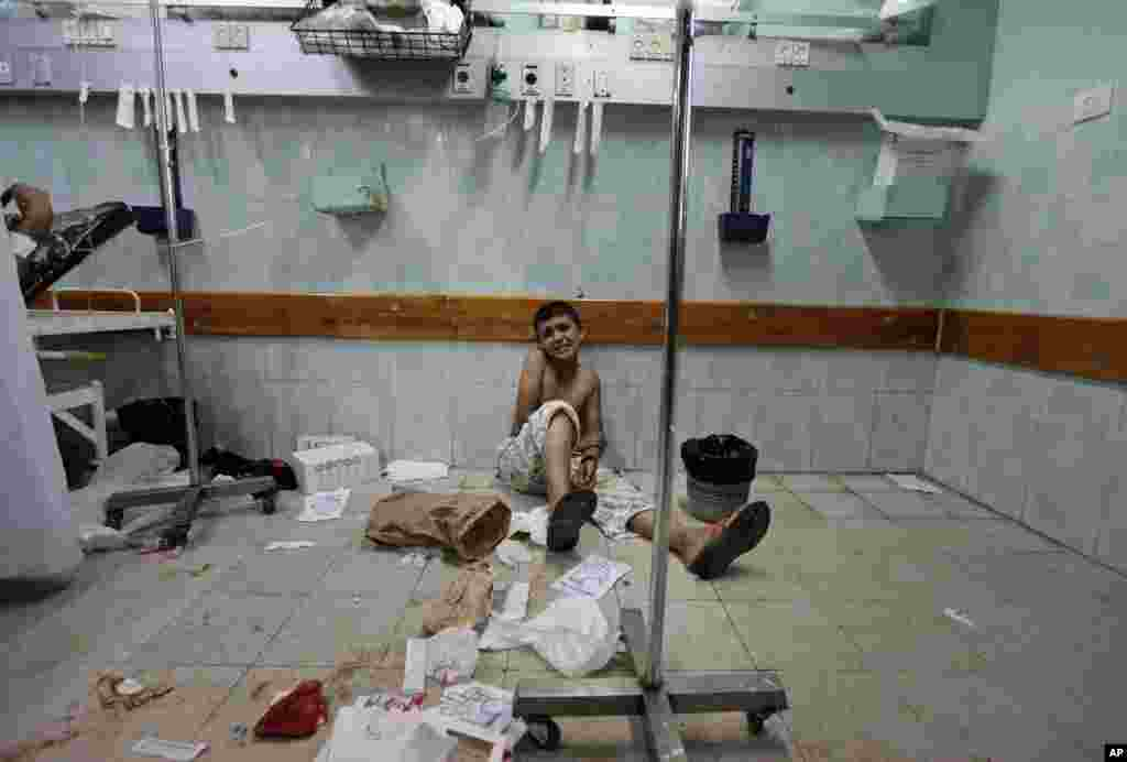 A Palestinian boy, who was wounded in an Israeli strike on a house in Beit Lahiya, northern Gaza Strip, sits on the floor as he waits to be treated at the emergency room of the Kamal Adwan hospital, in Beit Lahiya.