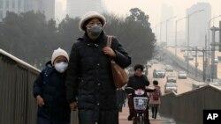 Los peatones se cubren la nariz para protegerse del aire contaminado de Beijing.
