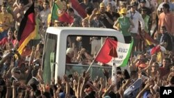 Pilgrims greet Pope Benedict XVI in his vehicle as he arrives at Cuatro Vientos, near to Madrid, Spain, August 21, 2011