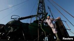 A technician of Cuba's state-run CUPET monopoly works on an oil pump in Havana, July 11, 2014.