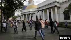 FILE - People walk past the National Assembly building in Caracas, Venezuela, Dec. 22, 2015.