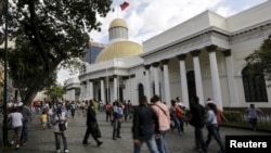 FILE - People walk past the National Assembly building in Caracas, Venezuela.