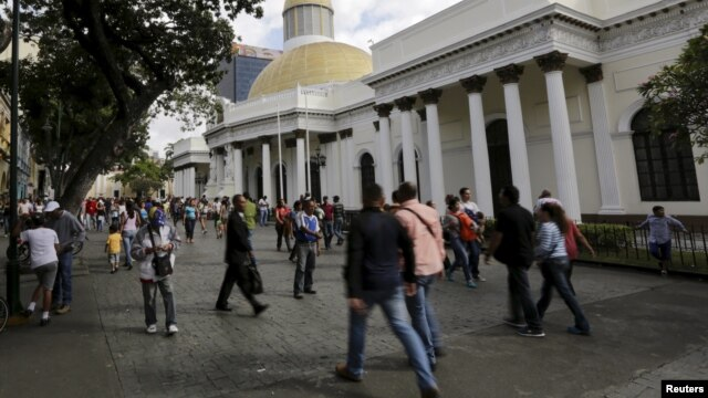 FILE - People walk past the National Assembly building in Caracas, Venezuela, Dec. 22, 2015.
