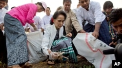 Leader of National League for Democracy party (NLD) Aung San Suu Kyi, front center, picks up garbage during a clean-up drive in Kawhmu, Myanmar, Dec. 13, 2015.