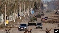Konvoi kendaraan lapis baja kelompok separatis yang didukung Rusia di Vuhlehirsk, dekat Debaltseve, Ukraina timur (22/2). (AP/Vadim Ghirda)