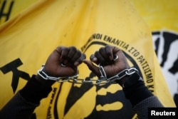 An African migrant living in Greece raises his chained hands during a protest against recent reports of migrant slavery in Libya, in Athens, Greece, Dec. 2, 2017.