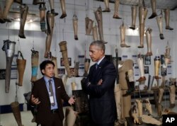 With prosthetics displayed behind him, U.S. President Barack Obama tours Cooperative Orthotic and Prosthetic Enterprise (COPE) Visitor Centre in Vientiane, Laos, Sept. 7, 2016.