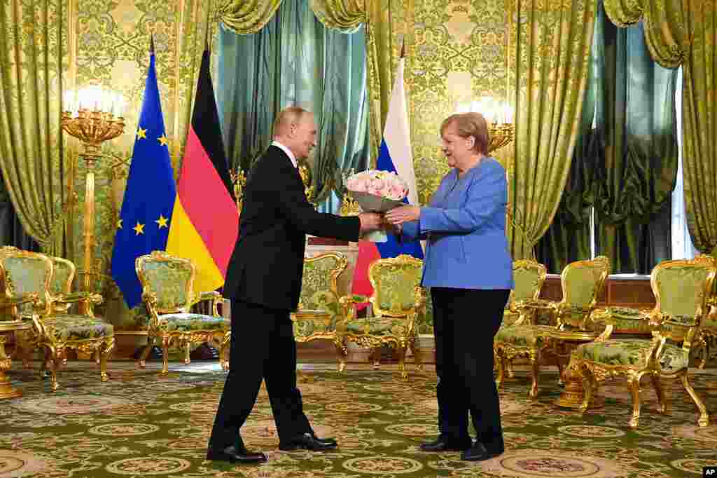 Russian President Vladimir Putin, left, presents flowers to German Chancellor Angela Merkel during their meeting in the Kremlin in Moscow, Russia.