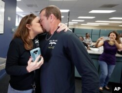 Former felon Brett DuVall, right, kisses his wife Dottie as they celebrate after he registered to vote at the Supervisor of Elections office, Jan. 8, 2019, in Orlando.