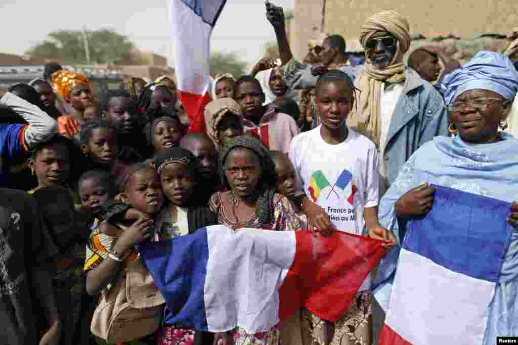 Children celebrate holding a French flag during the reopening ceremony of Mahamane Fondogoumo elementary school in the town center of Timbuktu February 1, 2013.
