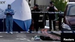 Petugas forensik dari kepolisian London tengah memeriksa lokasi kejadian dimana seorang pria tewas di Woolwich, London (22/5).