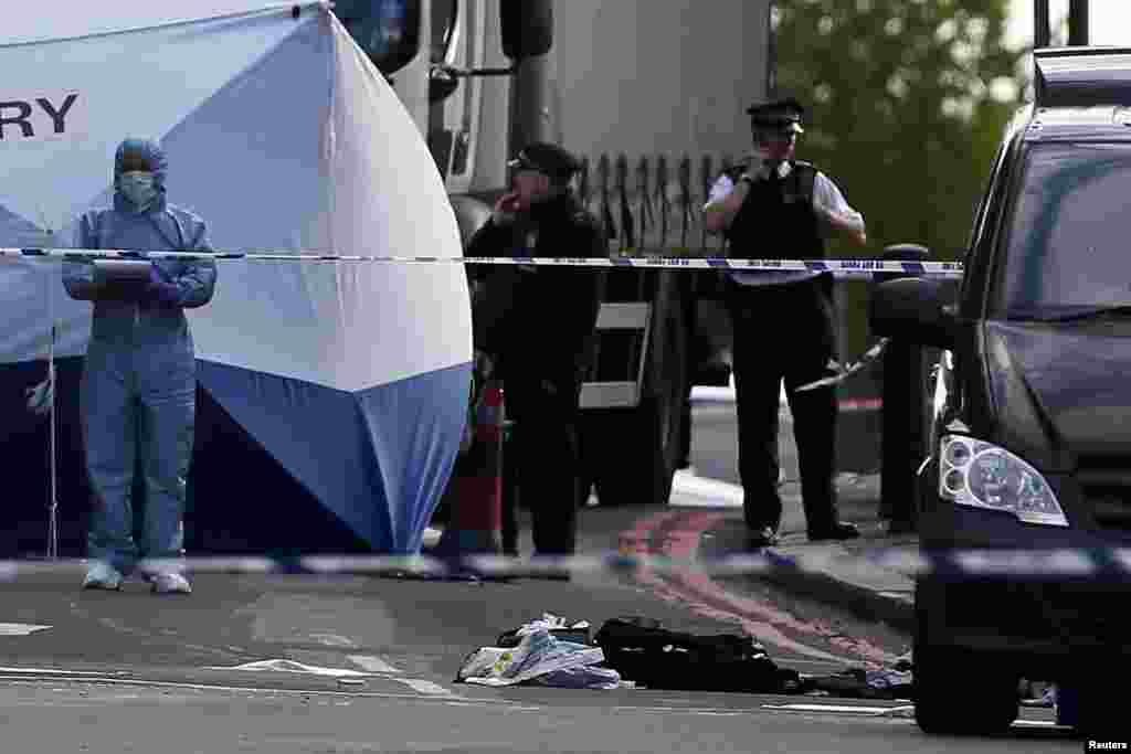 A police forensics officer investigates a crime scene where one man was killed in Woolwich, London, May 22, 2013.
