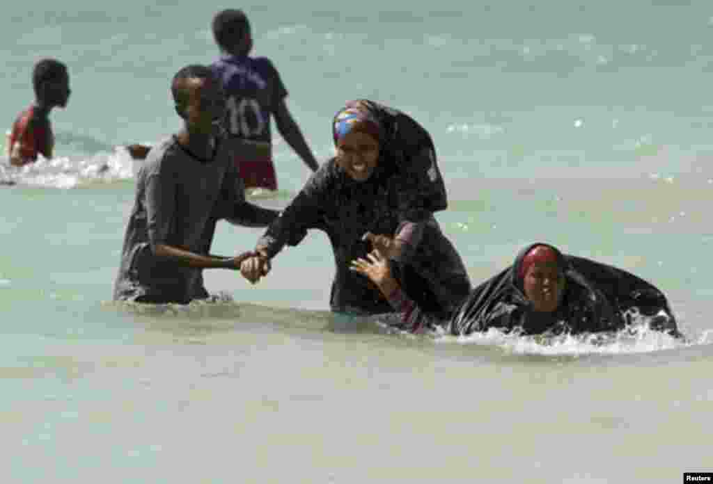 A man guides Somali women near Lido beach in the waters of the Indian Ocean, north of the capital Mogadishu January 6, 2012. Lido beach was a famous attraction before Somalia tumbled into chaos in 1991 with the ousting of dictator Mohamed Siad Barre. In t