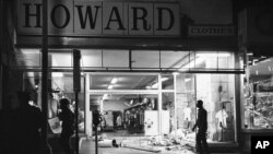 FILE- In this April 4, 1968 file photo, glass and mannequins litter a sidewalk of a clothing store in Northwest Washington after crowds broke into and took items from some stores following the news of Dr. Martin Luther King Jr.'s assassination. (AP Photo/Charles Harrity)