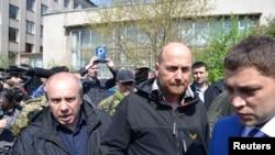 Pengamat OSCE Axel Schneider (tengah) dikawal ketat seusai dibebaskan oleh separatis pro-Rusia yang menahannya sejak bulan lalu di kota Slaviansk, Ukraina Timur (3/5).